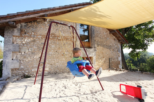 Sandpit swing, toddler playing on holiday in France